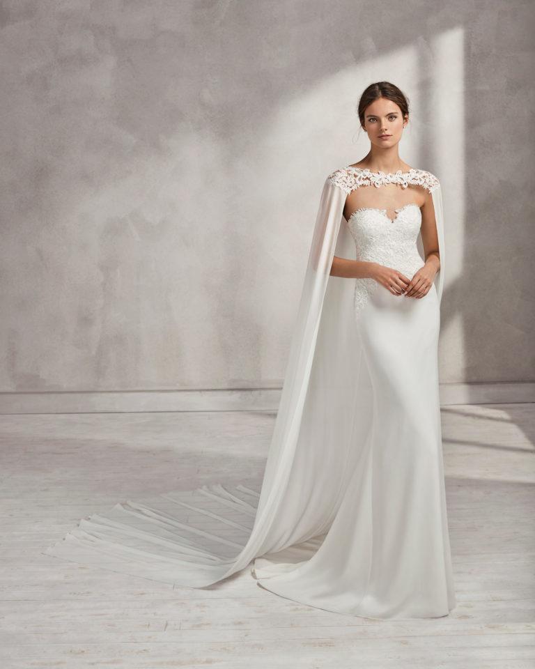 Vestido de novia corte sirena con capa en georgette y guipur, con escote corazón.