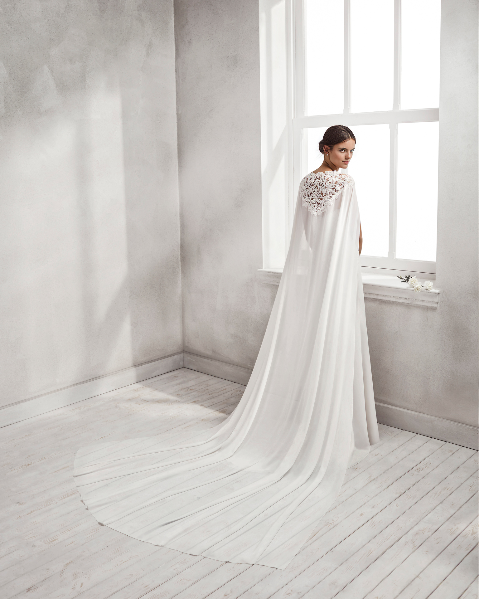 Mermaid-style crepe Georgette and guipure lace wedding dress with sweetheart neckline and cape.