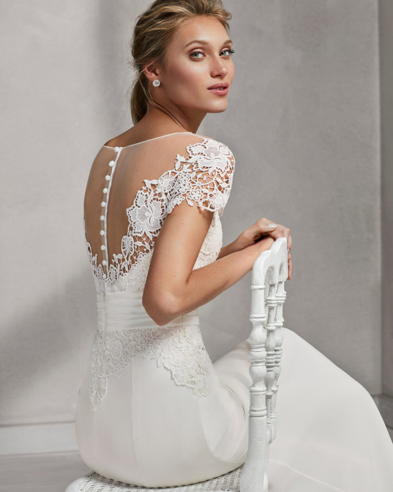 Mermaid-style crepe Georgette and guipure lace wedding dress with off-the-shoulder neckline.