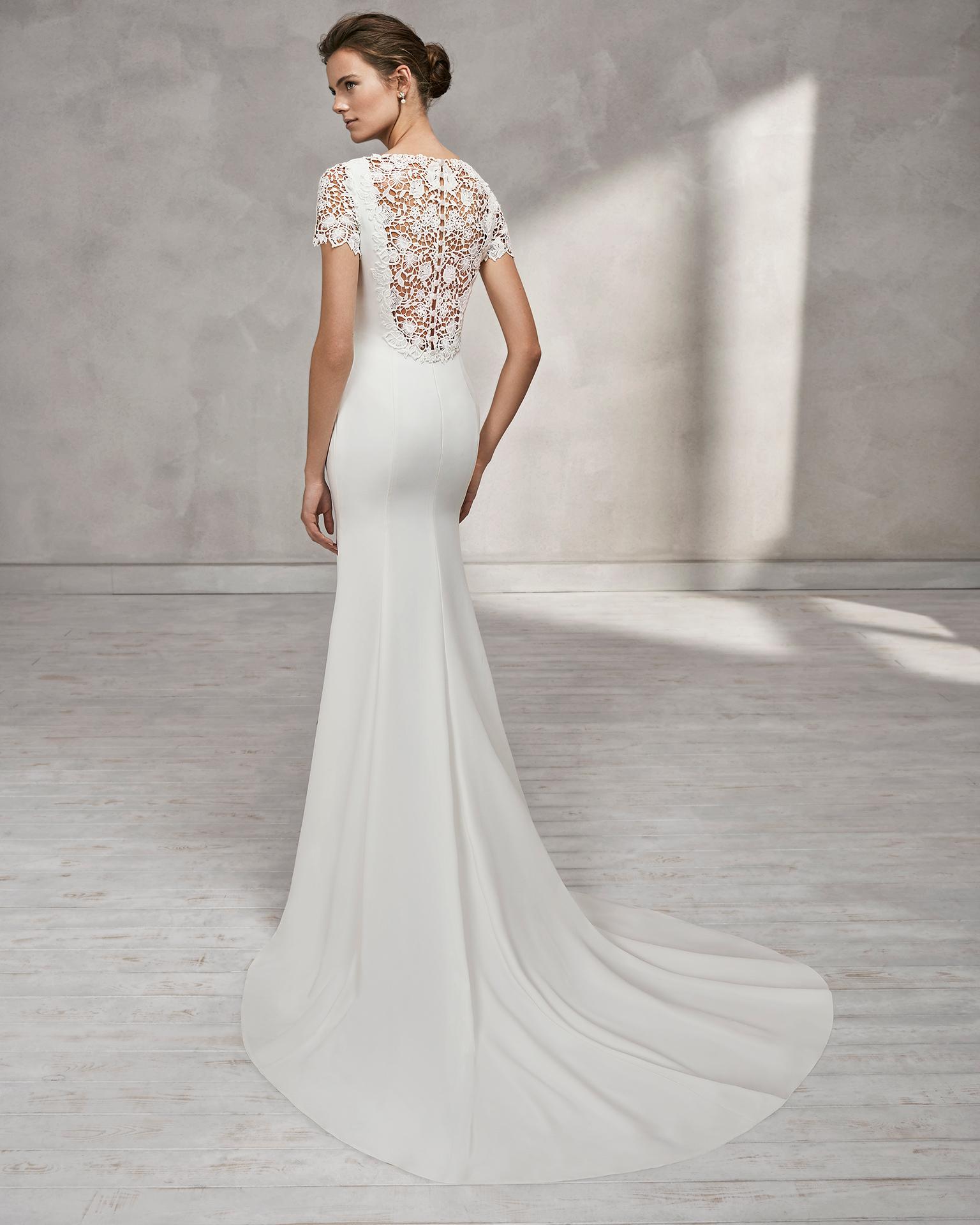 Vestido de novia corte sirena en crepe de manga corta con escote barco y espalda en guipur.
