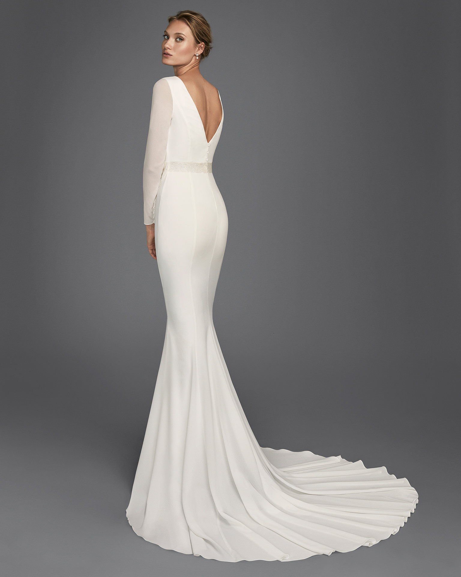 Mermaid-style crepe Georgette wedding dress with long sleeves and V-back with bow and beaded appliqués.