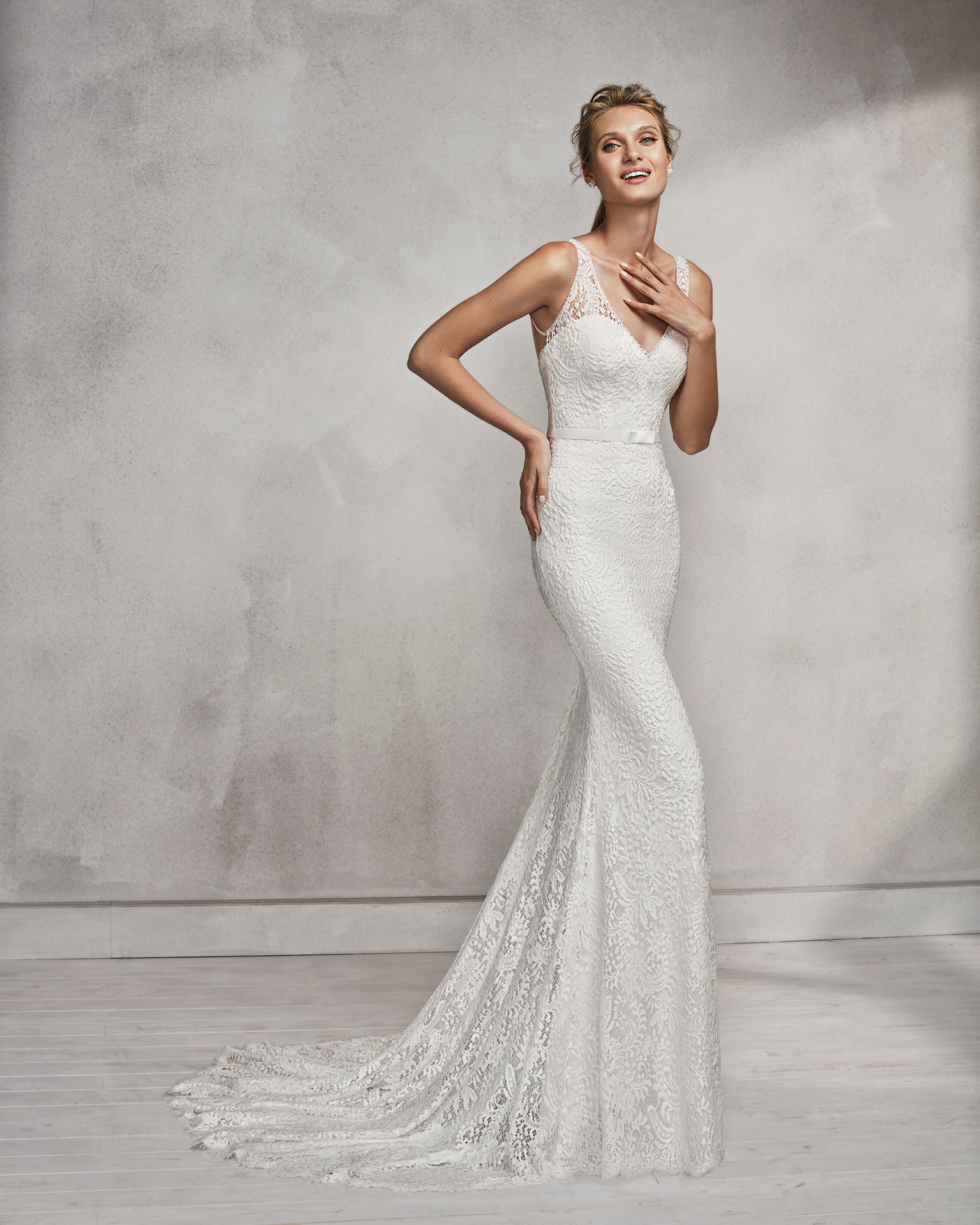 Mermaid-style beaded lace wedding dress with V-neckline and low back.