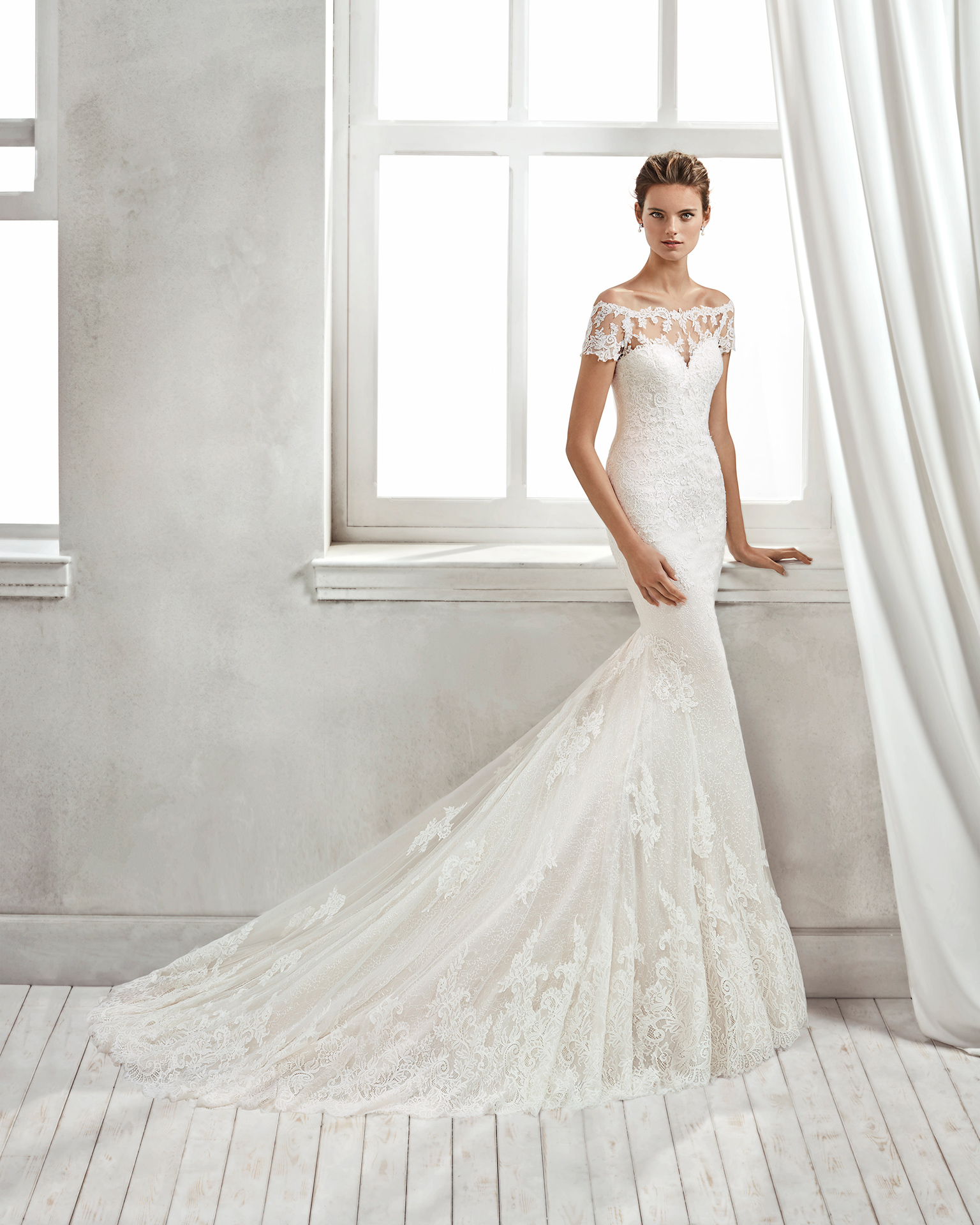 Mermaid-style lace wedding dress with off-the-shoulder neckline and lace appliqués, in nude and natural.