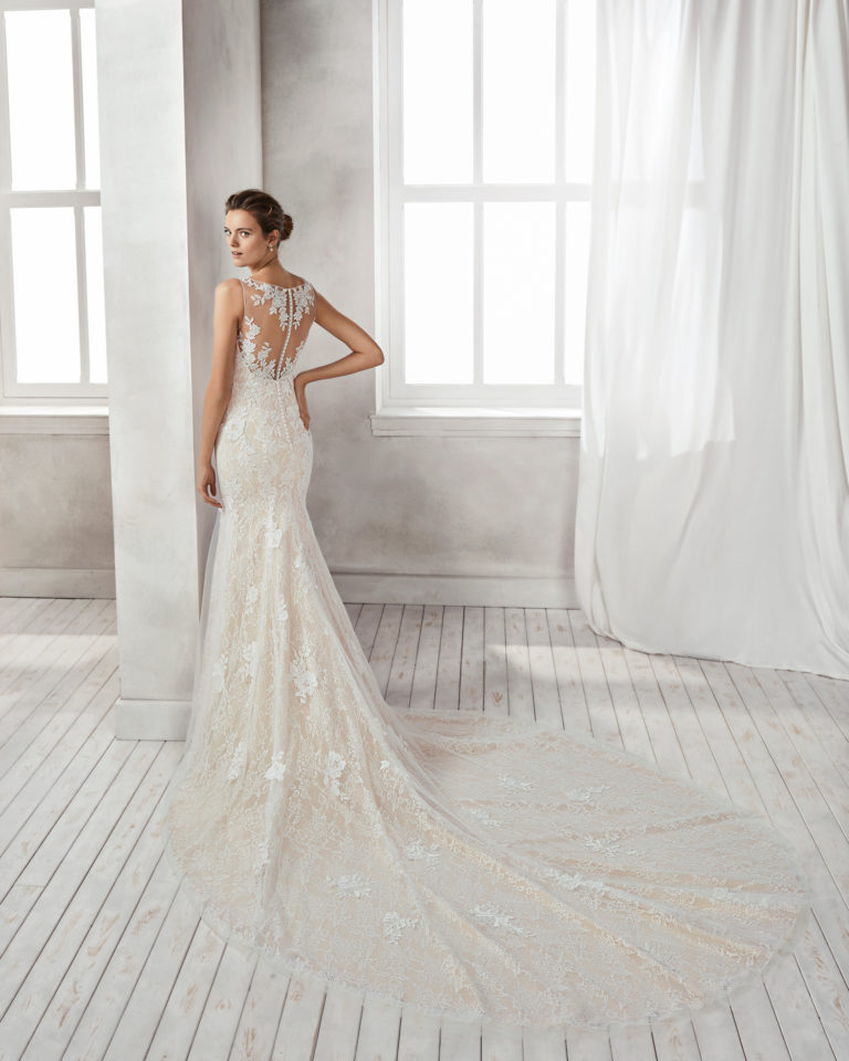 Vestido de novia corte sirena en encaje y pedreria, con escote V en color nude y natural.