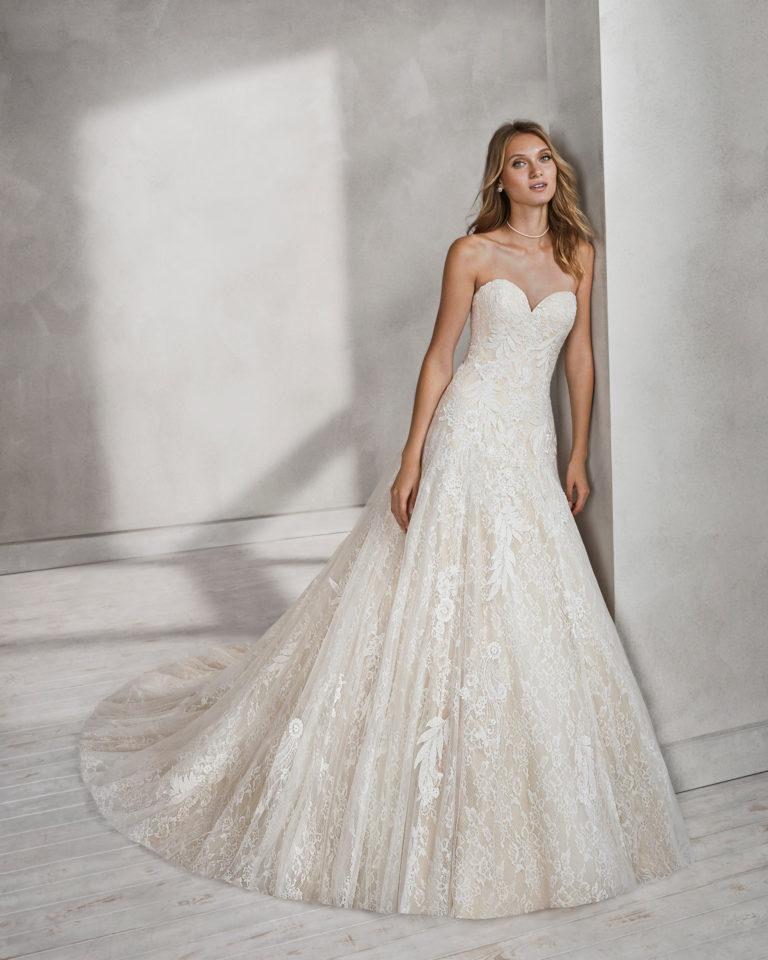 Vestido de novia estilo línea A en encaje y pedreria con escote corazón en color nude y en natural.