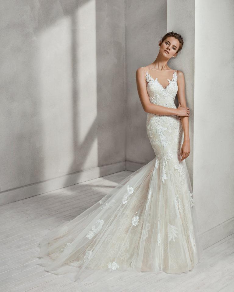 Vestido de novia corte sirena en encaje, pedrería y tul, con escote V y espalda escotada en color nude y en natural con sobrefalda.