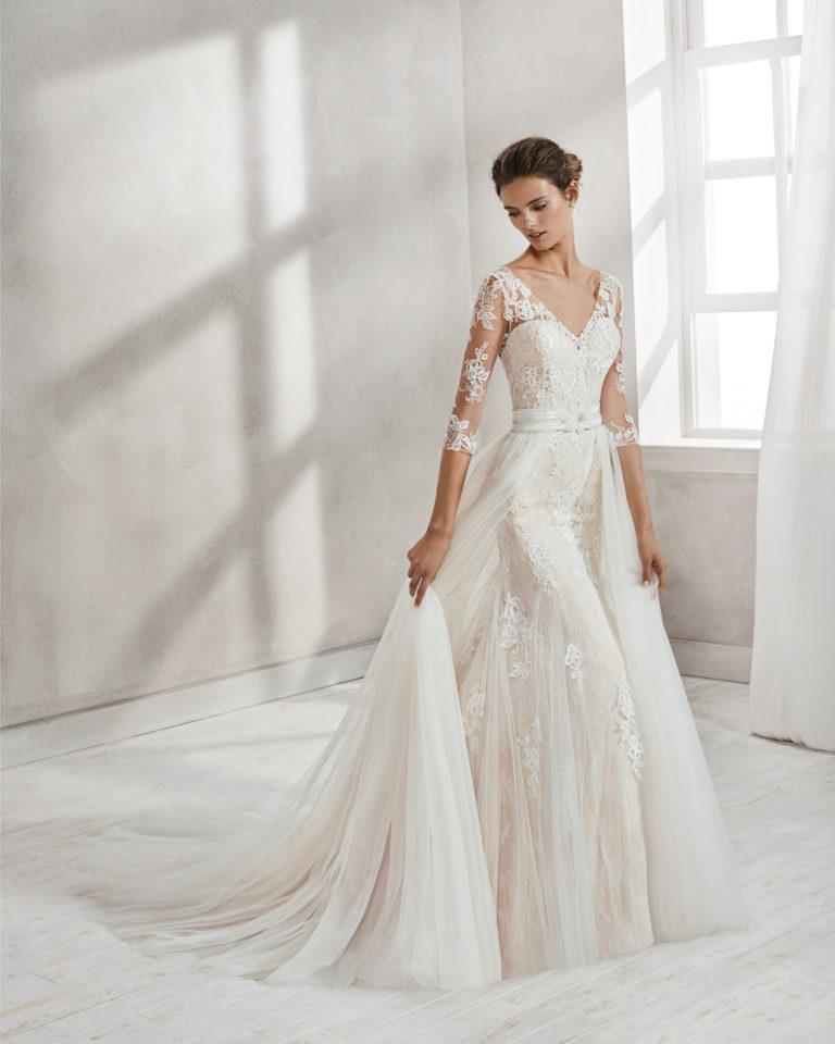 Vestido de novia corte sirena en encaje y pedreria. De manga francesa con escote V y espalda escotada, con sobrefalda de tul en color nude y en natural.