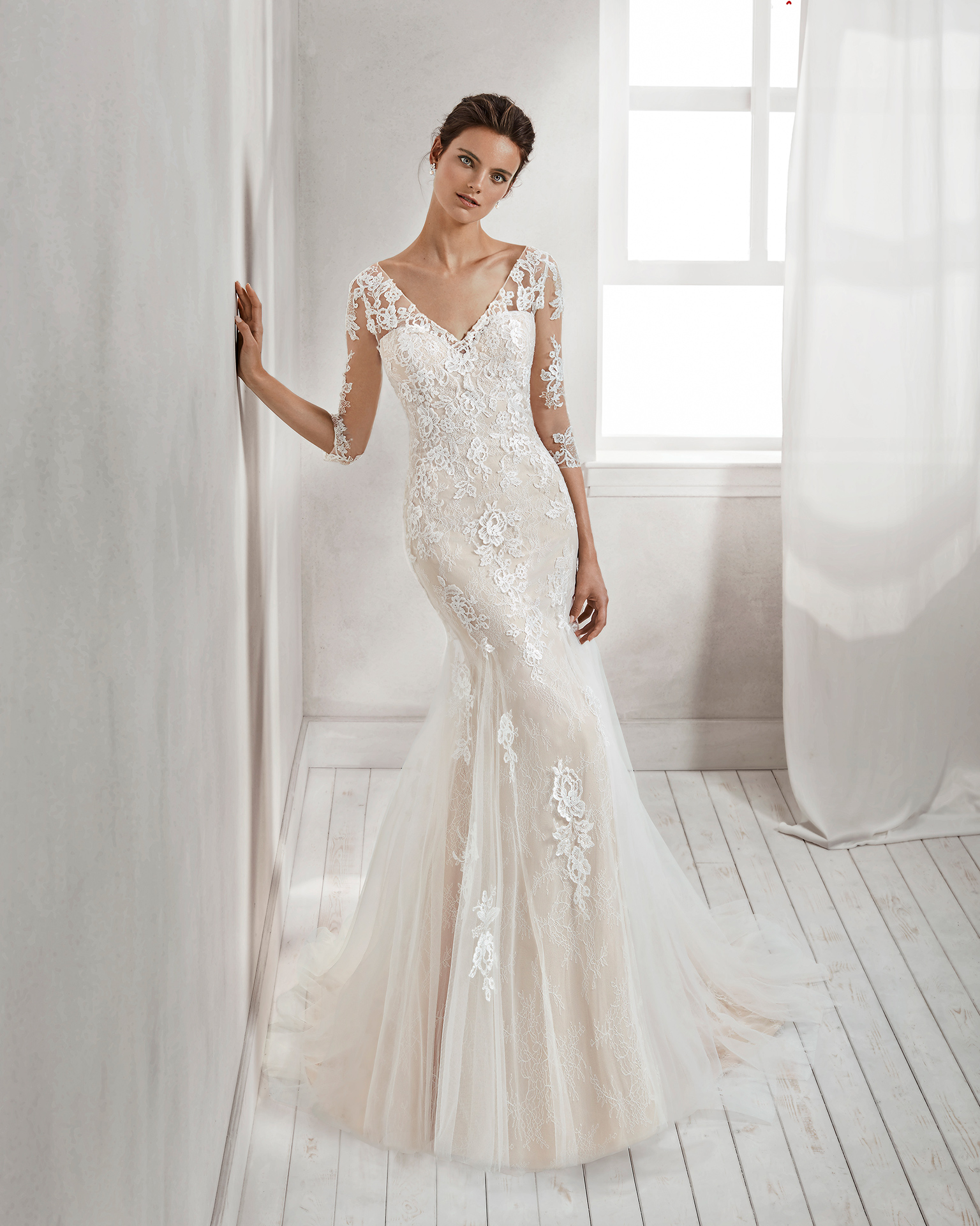 Mermaid-style beaded lace wedding dress with three-quarter sleeves, V-neckline, low back and tulle overskirt, in nude and natural.