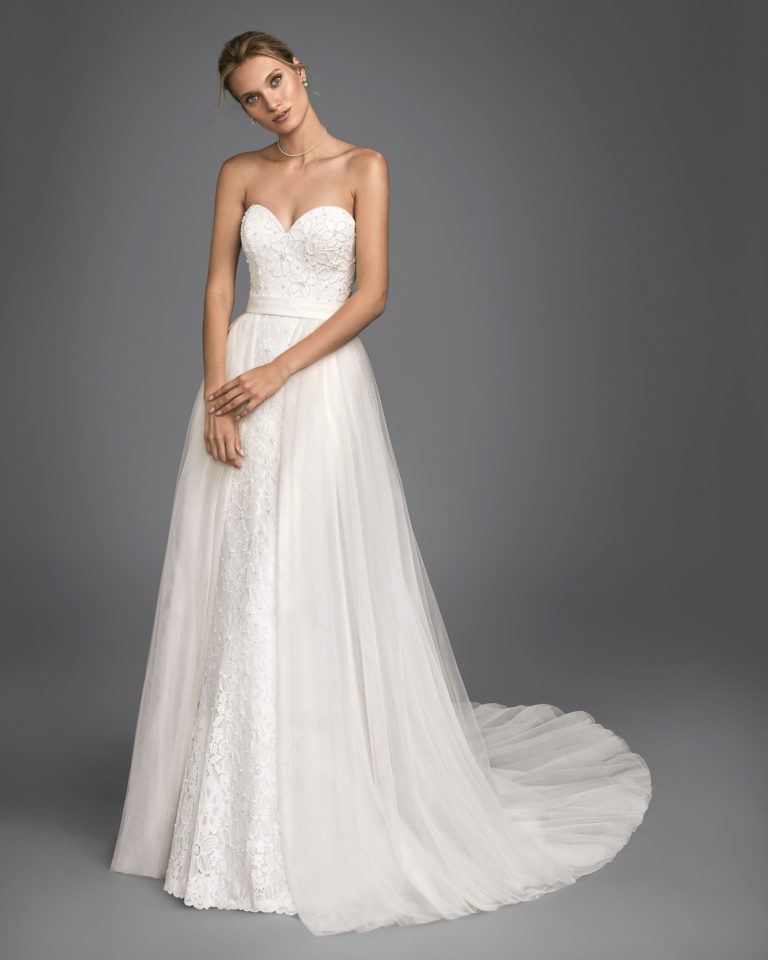 Mermaid-style beaded lace wedding dress with sweetheart neckline and tulle overskirt.