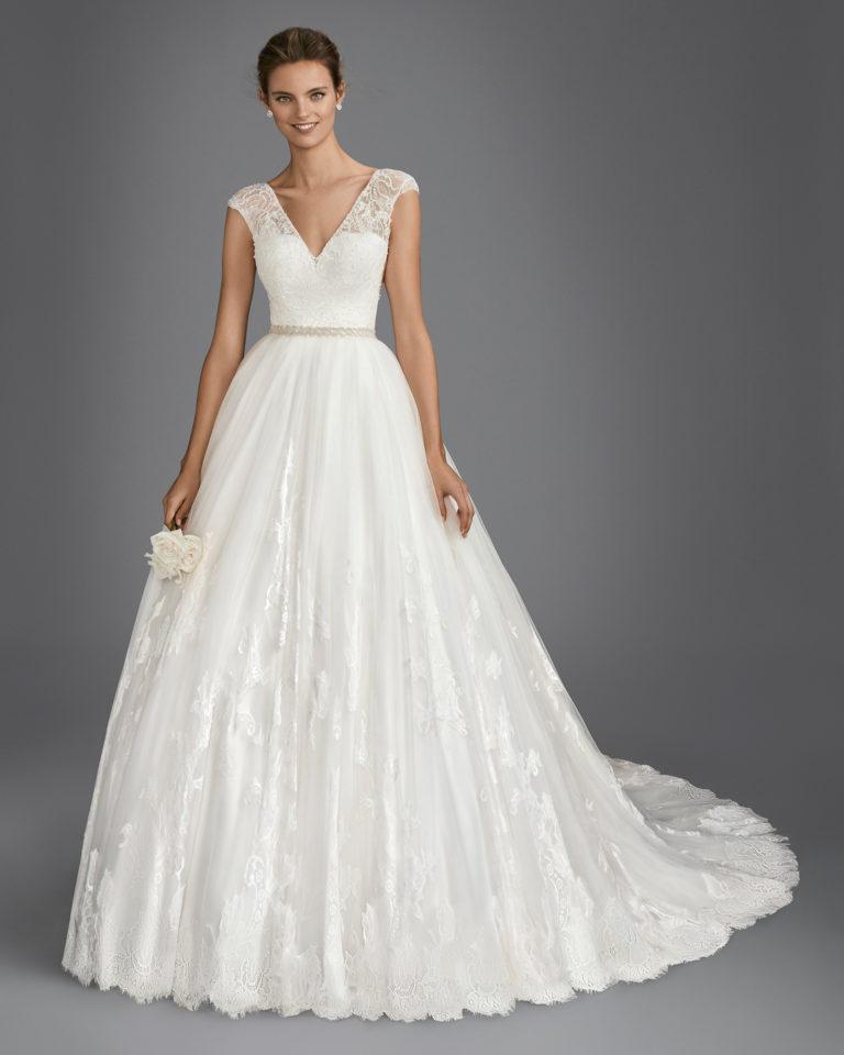 Vestido de novia estilo línea A en encaje, pedrería y tul, con escote V y espalda escotada en color natural y blanco.