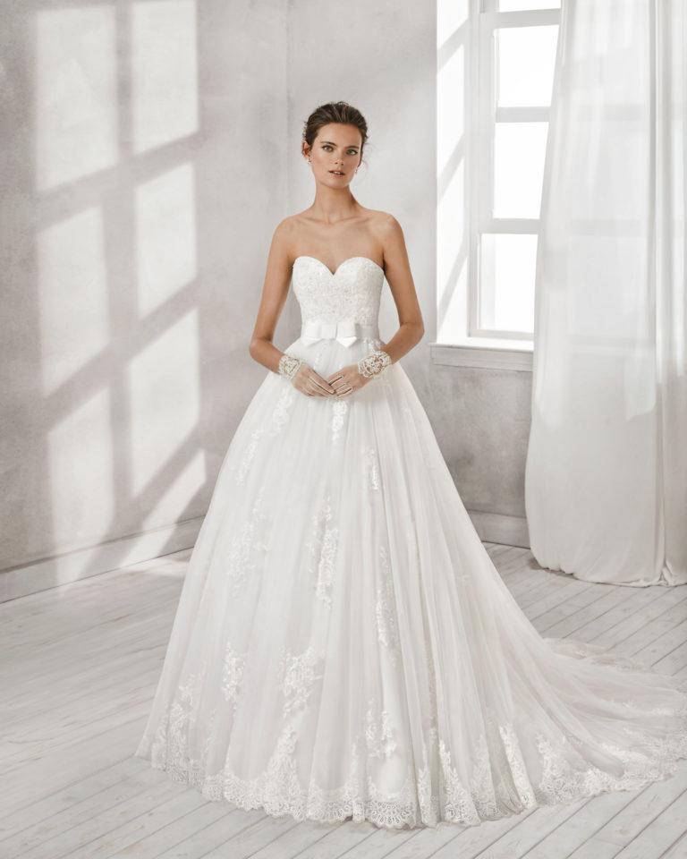 Vestido de novia estilo línea A en encaje, pedrería y tul, con escote corazón con lazo en la cintura.