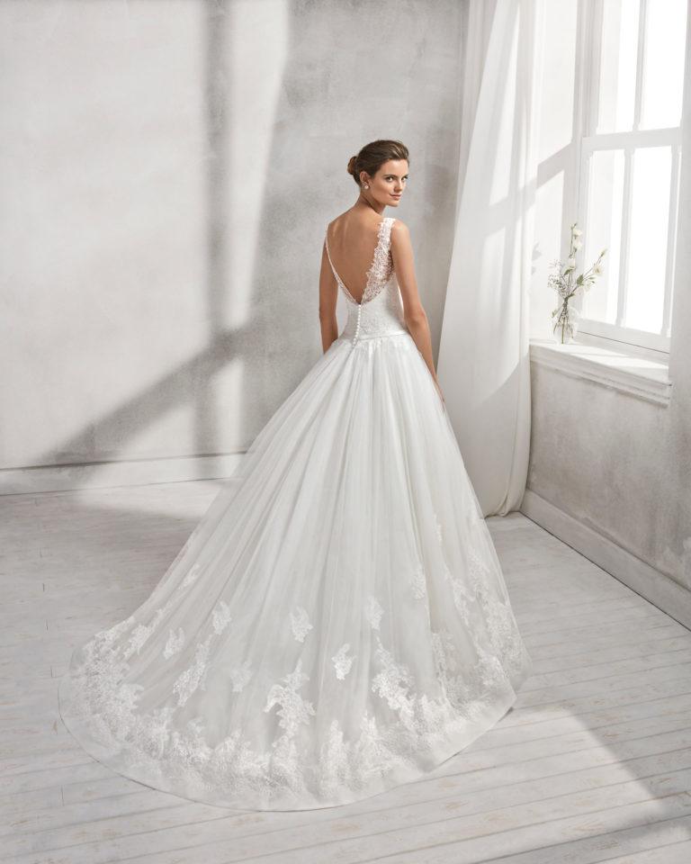 Vestido de novia estilo línea A en encaje, pedrería y tul, con escote V y espalda escotada.