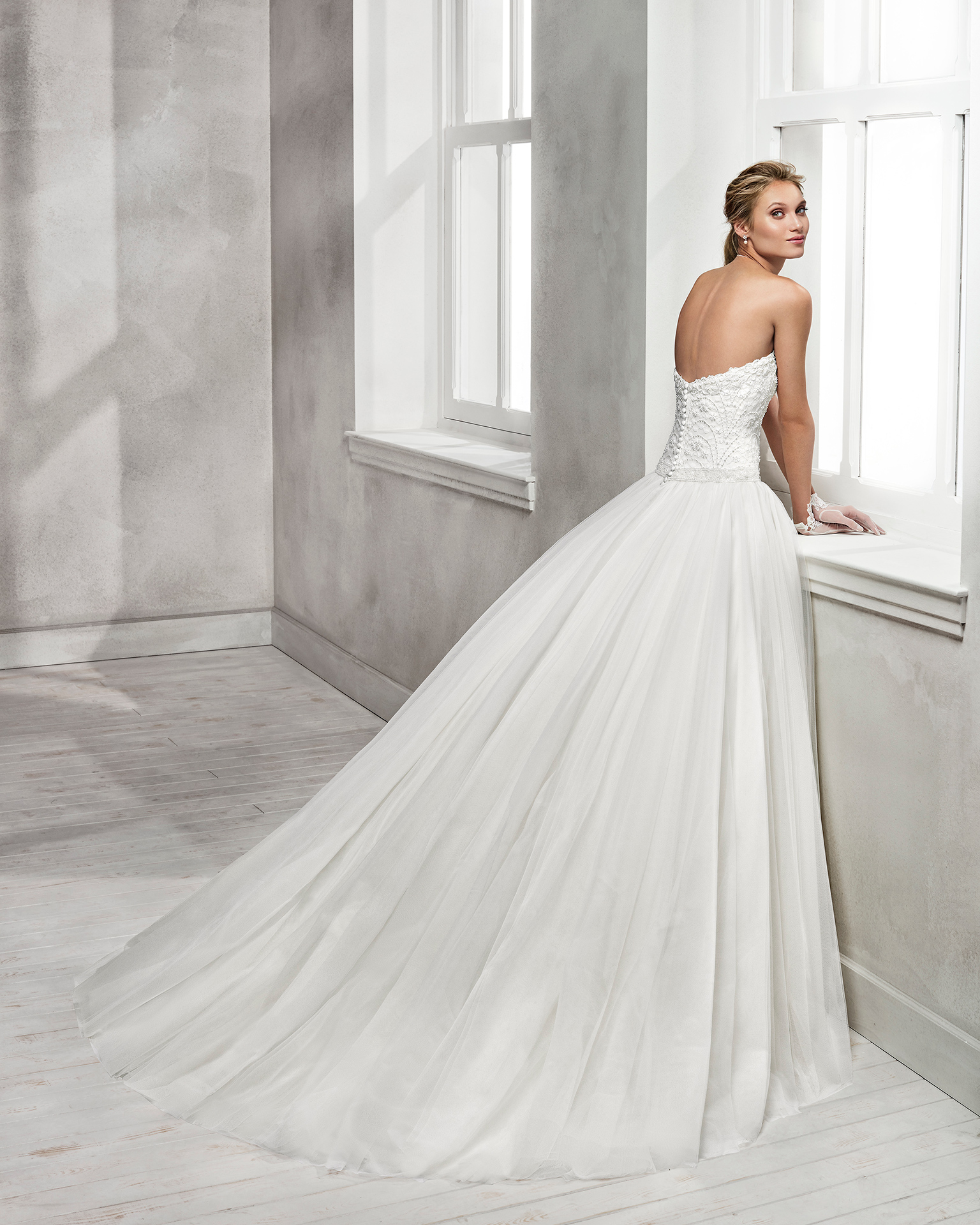 Vestido de novia estilo romántico en tul, encaje y pedreria, con escote palabra de honor.