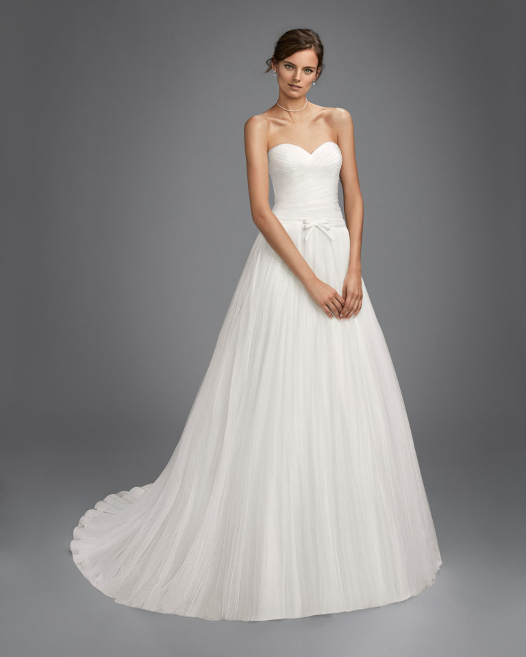 Romantic-style tulle wedding dress with sweetheart neckline and bow at waist.