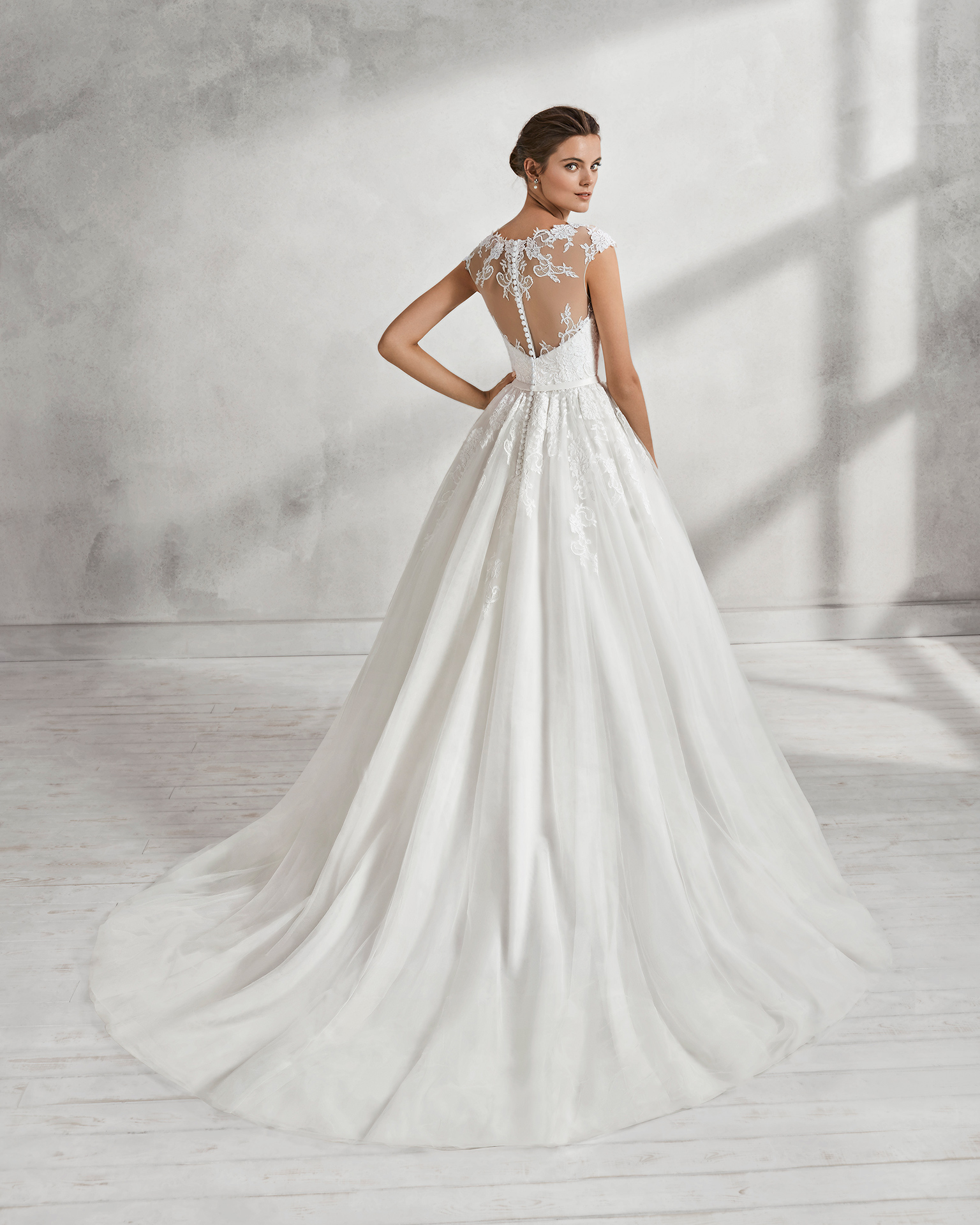 Romantic-style tulle and lace wedding dress with illusion neckline, low back and beaded appliqués, in natural and white.