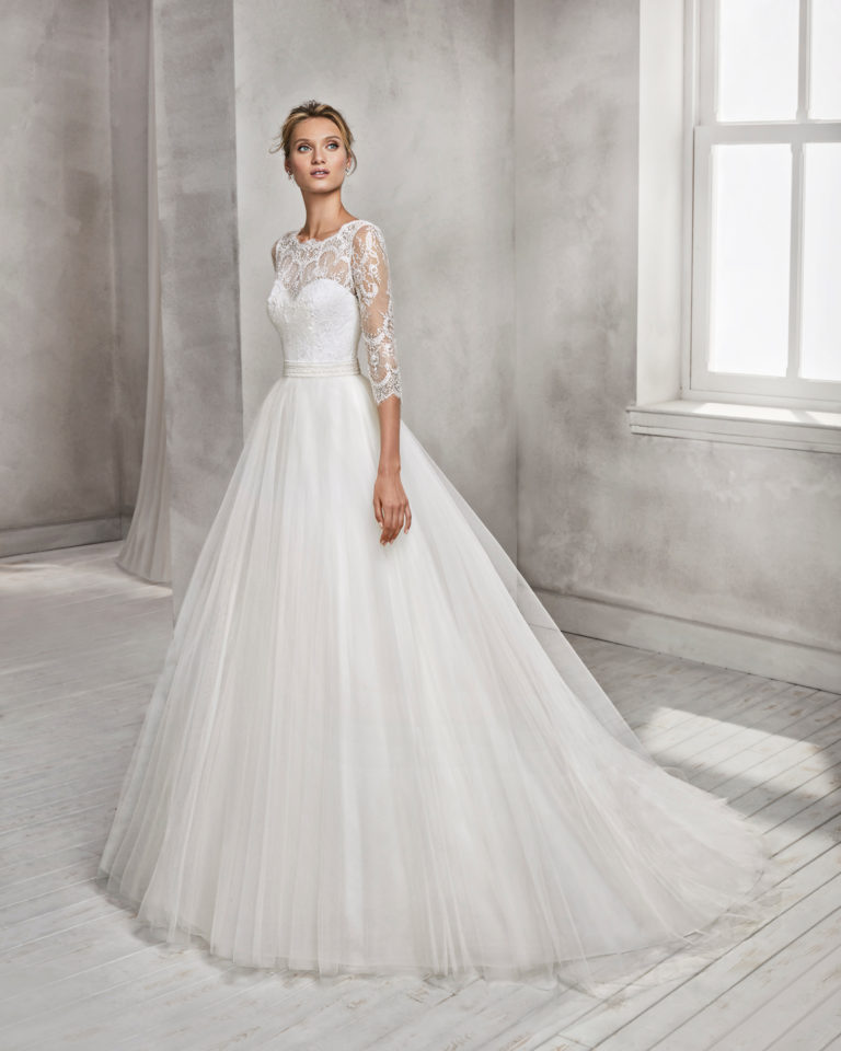 Princess style beaded lace and tulle wedding dress with three-quarter sleeves and illusion neckline.