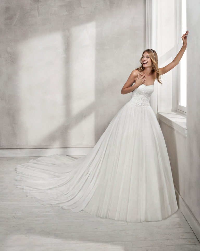 Princess-style beaded lace and tulle strapless wedding dress with full tulle skirt.