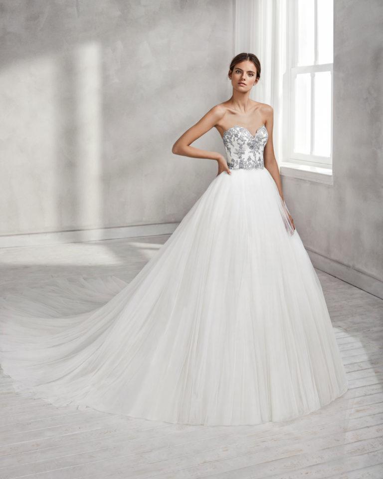 Vestido de novia estilo princesa, en encaje con escote corazón, y falda de tul con volumen en color natural/plata y en natural.