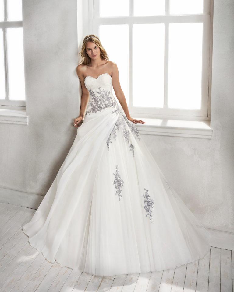 Vestido de novia estilo princesa en organza y tul, con escote corazón y aplicaciones de encaje en color natural/plata y en natural.