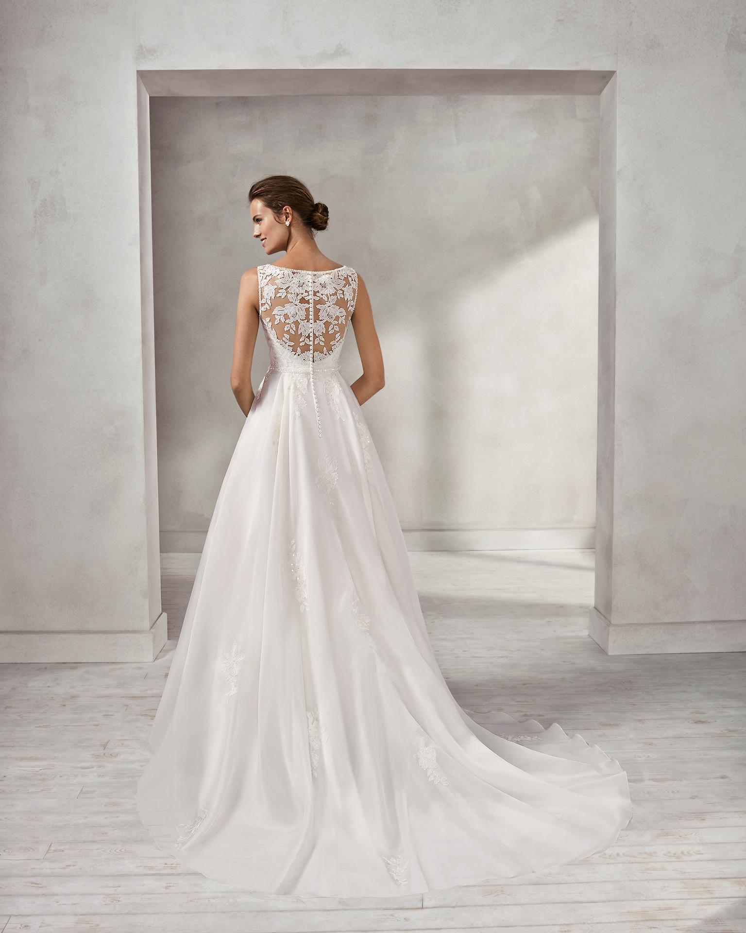 Vestido de novia estilo princesa en organza, encaje y pedreria, con escote ilusión con espalda de encaje y pedreria.