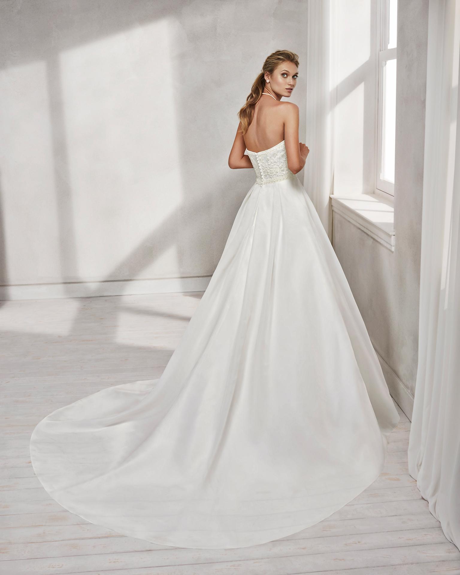Vestido de novia estilo línea A en organza bordada, con pedrería con escote corazón.