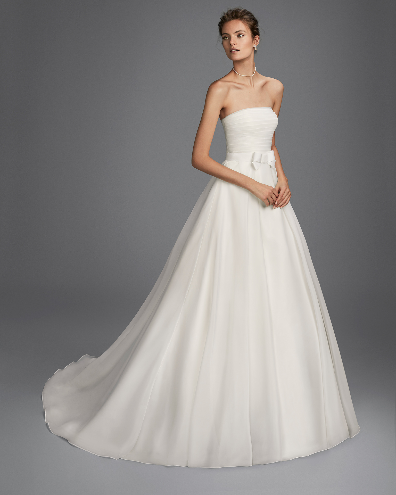 A-line organza strapless wedding dress with bow at waist.