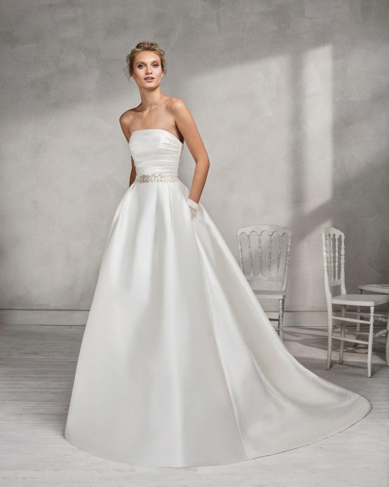 Vestido de novia estilo clásico en mikado, con escote palabra de honor con cinturón de pedrería.