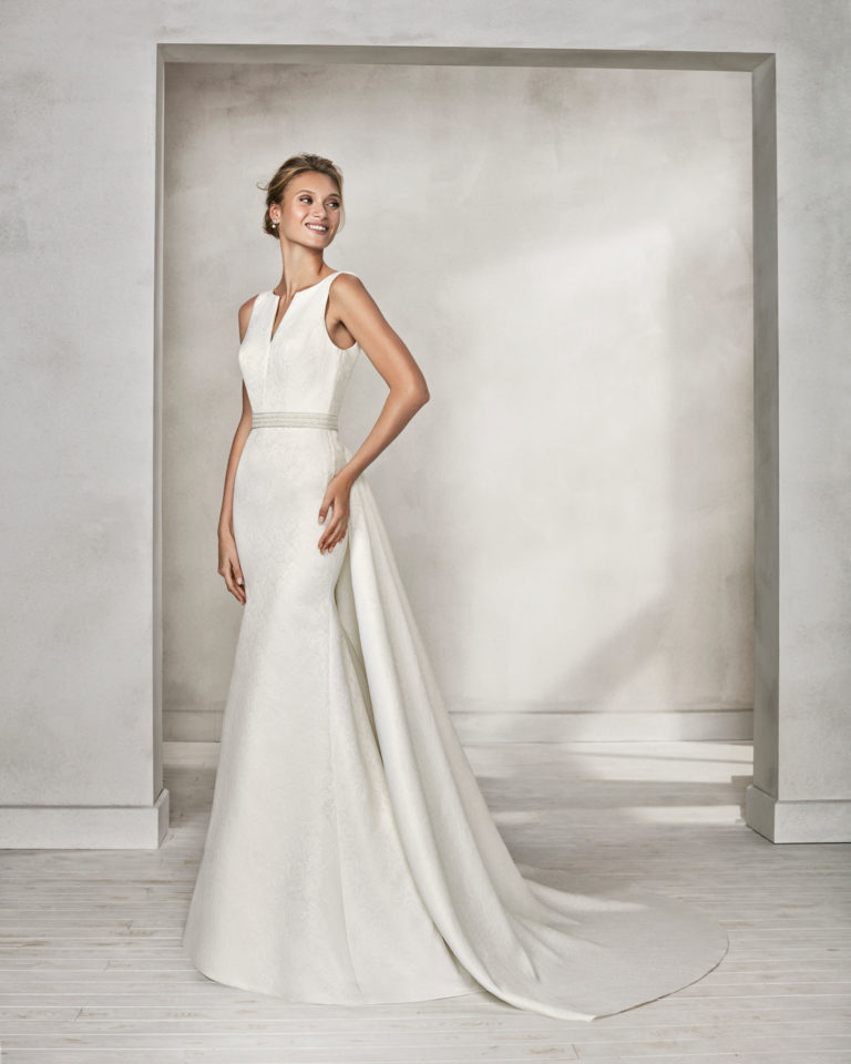 Mermaid-style beaded brocade wedding dress with bateau neckline and train.