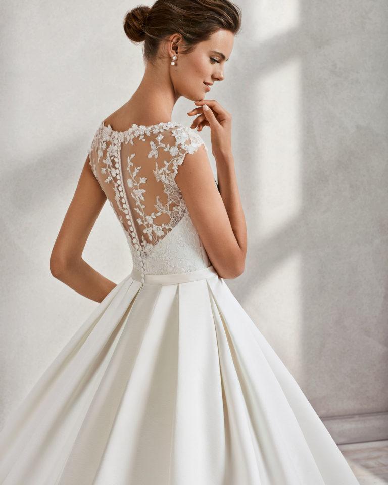 Vestido de novia estilo clásico en raso duquesa, encaje y pedreria, con escote ilusión en color marfil.