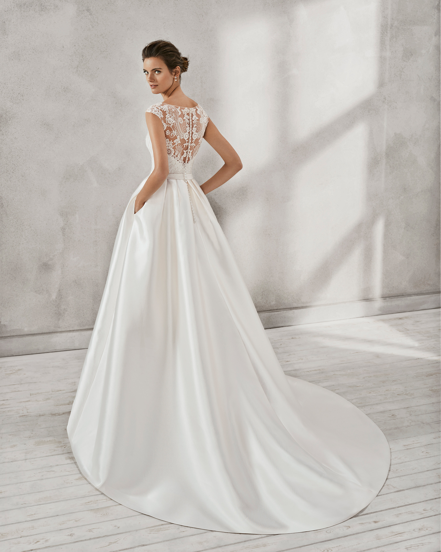 Classic-style beaded lace and mikado wedding dress with illusion neckline.