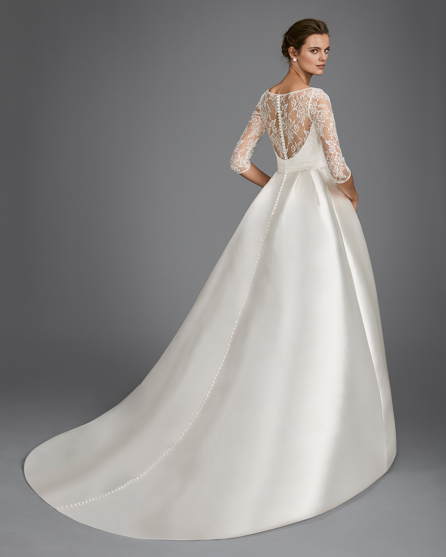 Classic-style beaded lace and mikado wedding dress with three-quarter sleeves and illusion neckline.