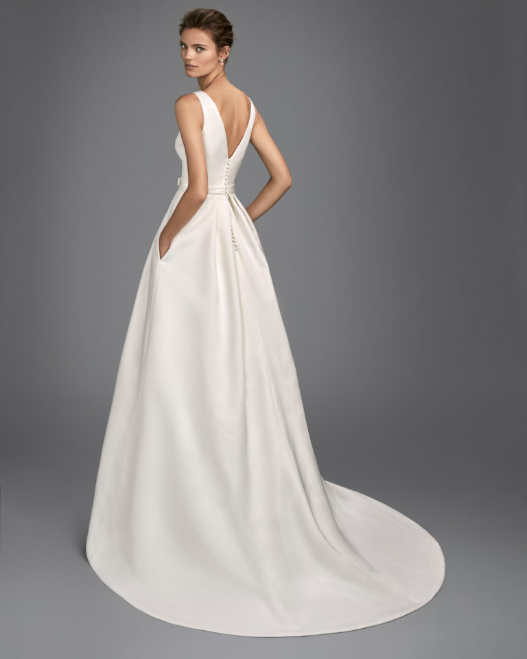 Classic-style piqué wedding dress with bateau neckline, V-back and bow at waist.