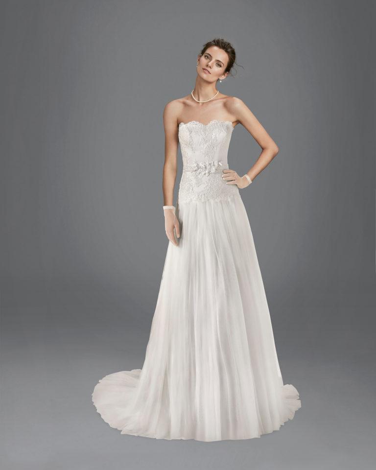 Vestido de novia de corte recto en tul suave, encaje y pedrería, con escote semi-corazón y adorno en cintura, disponible en color natural y blanco.