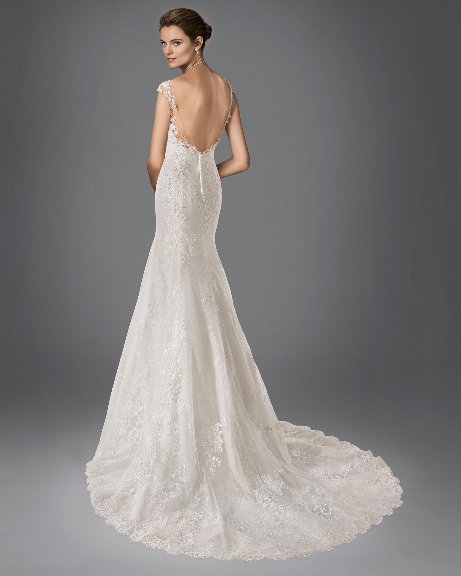 Vestido de novia de corte sirena en tul, encaje y pedrería con escote pico y aplicaciones de encaje, disponible en color nude y natural.