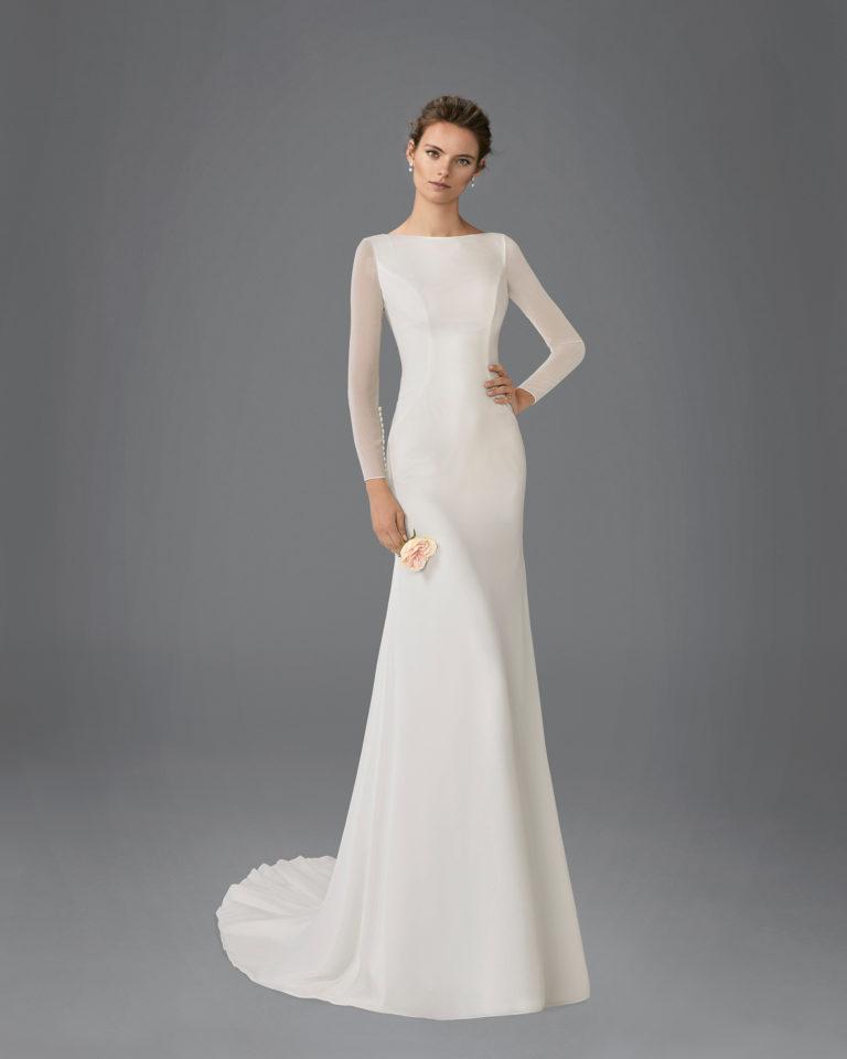 Vestido de novia de corte recto en georgette con escote barco, espalda pico y manga largas.