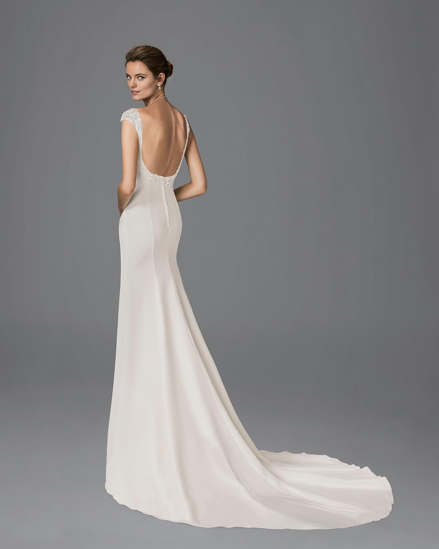 Vestido de novia de corte recto con arrastre en crepe, con escote barco y espalda joya de pedrería frost.