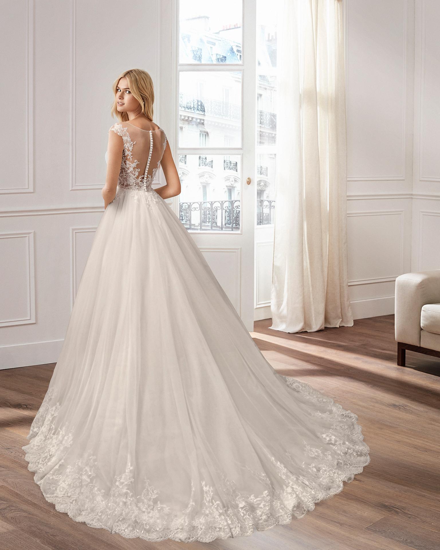 Vestido de novia estilo línea A en tul, encaje y pedrería, con escote V y espalda escotada.