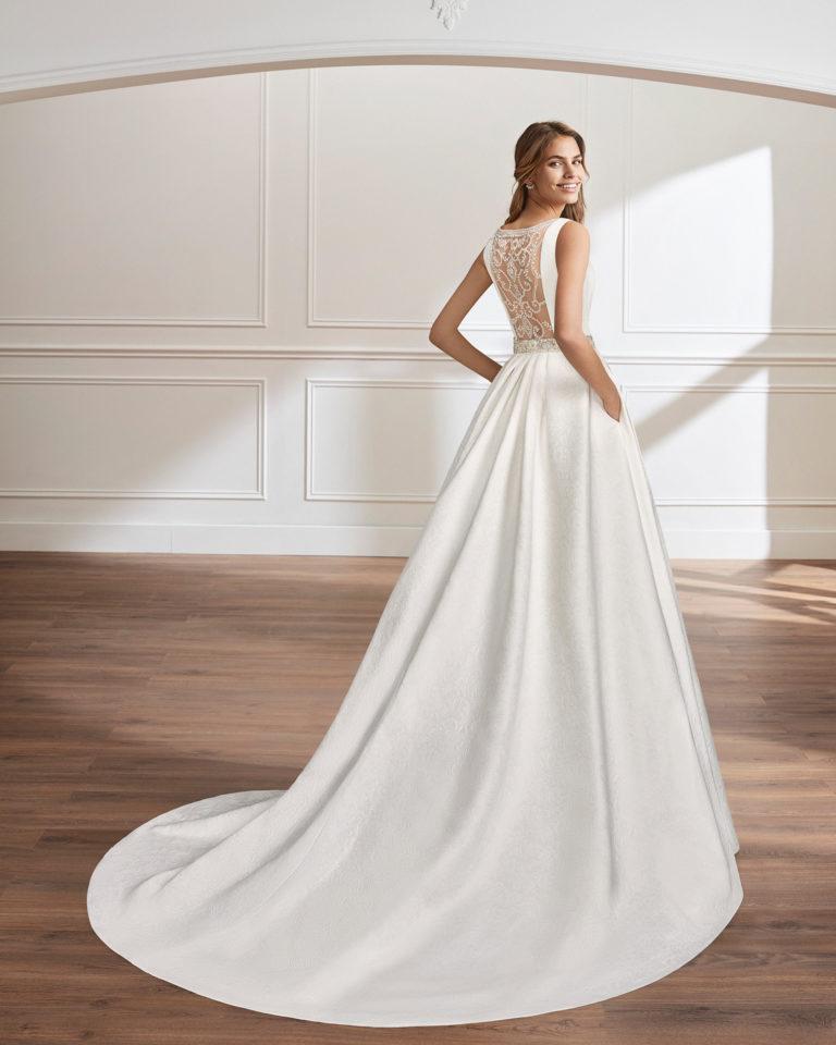 Classic-style beaded brocade wedding dress with bateau neckline, pockets, beaded back and beaded appliqués.