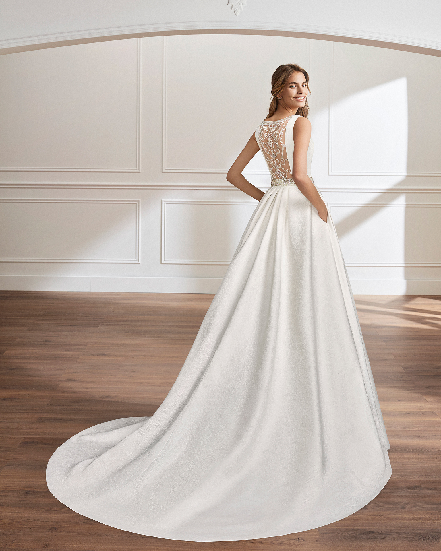 Classic-style beaded brocade wedding dress with bateau neckline, pockets, beaded back and beaded appliqués.