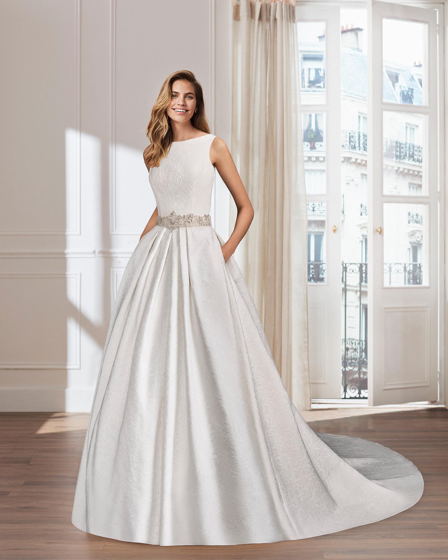 Vestido de novia estilo clásico en brocado y pedreria. Escote barco con espalda y apliques de pedreria con bolsillos.
