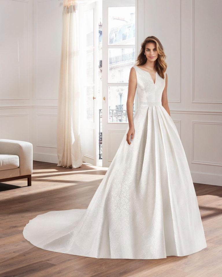 Vestido de novia corte clásico línea A, en brocado con escote pico en delantero y espalda.