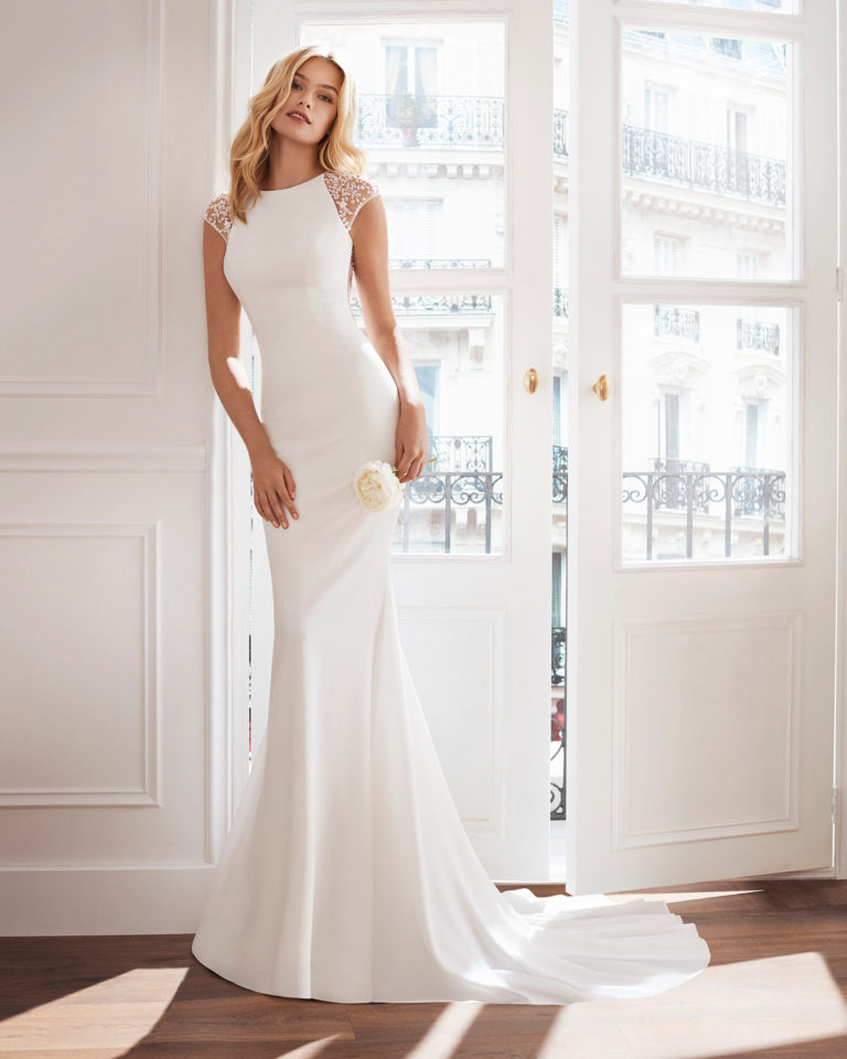 Sheath-style wedding dress in crepe. Sleeveless, with square neckline, train and jewelled back. Available in natural. 2019  Collection.