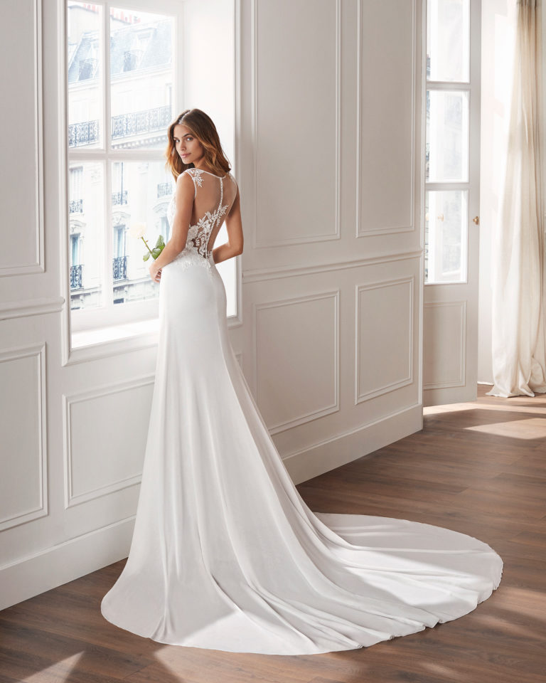 Sheath-style wedding dress in crepe Georgette. Sleeveless lace bodice with illusion neckline and train. Available in natural. 2019  Collection.