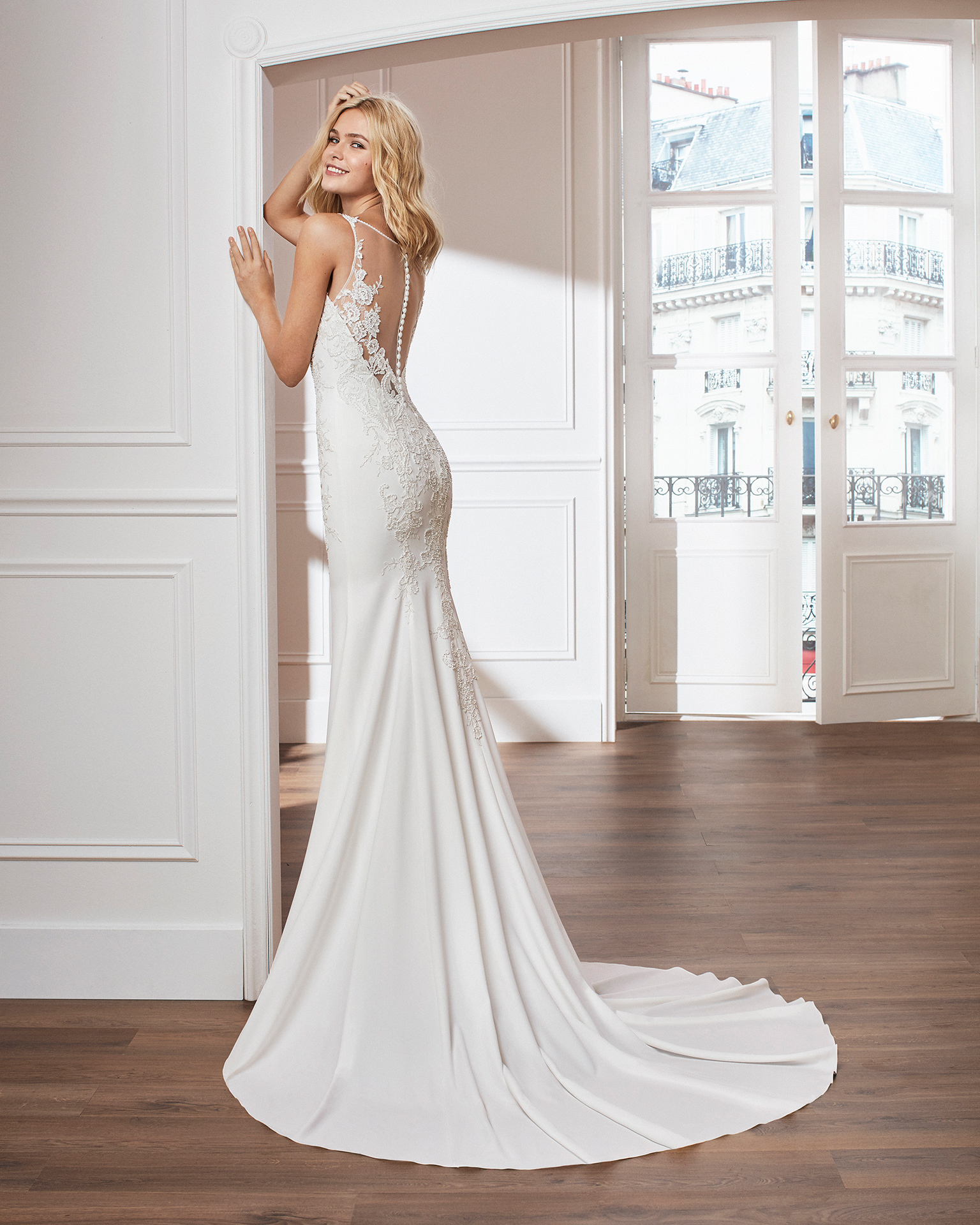Sheath-style wedding dress in crepe. Sleeveless V-neck beaded lace bodice with train. Available in natural. 2019  Collection.