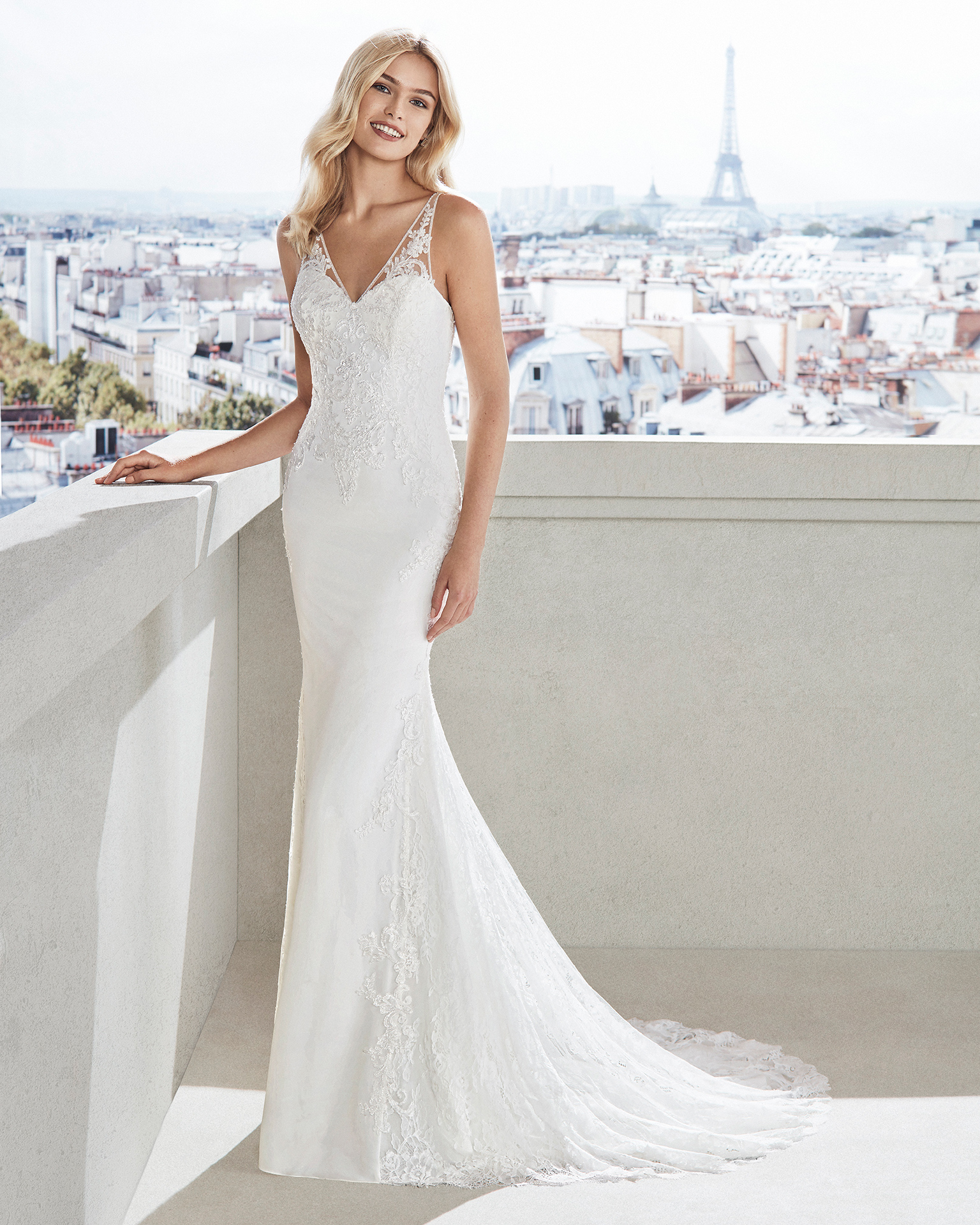 Sheath-style wedding dress in crepe. Beaded lace bodice, V-neckline and train edged with lace. Available in natural. 2019  Collection.