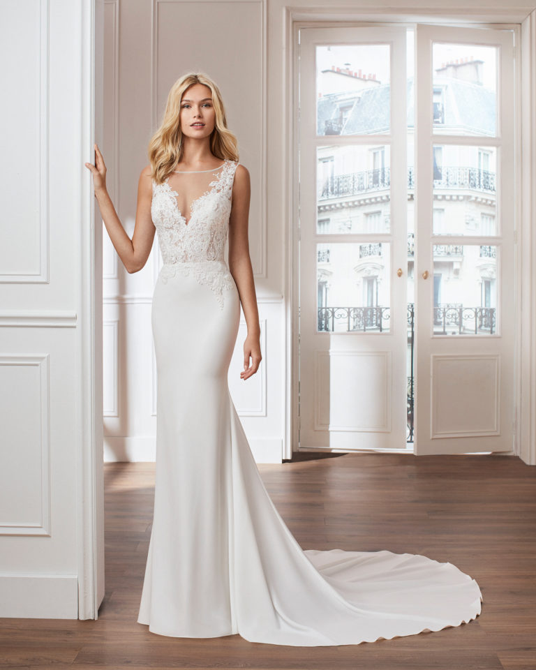 Sheath-style wedding dress in crepe. V-neck beaded lace bodice and train. Available in natural. 2019  Collection.