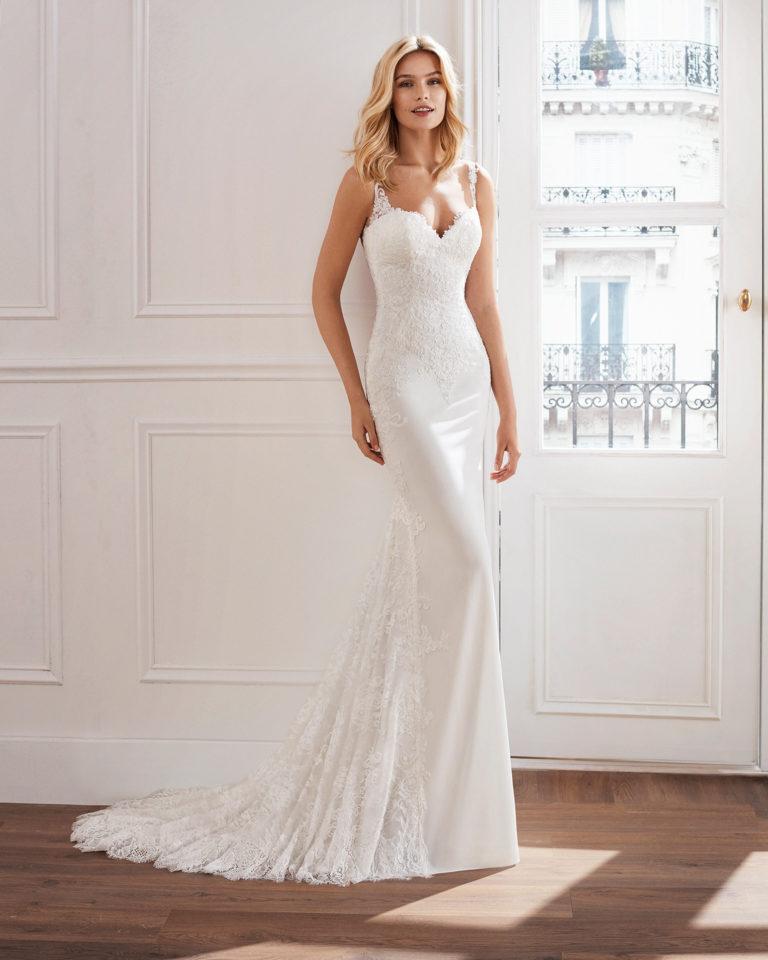 Vestido de novia corte recto en crepe. Con cuerpo de encaje con pedrería y encaje incrustado en la falda. Disponible en color natural. Colección  2019.