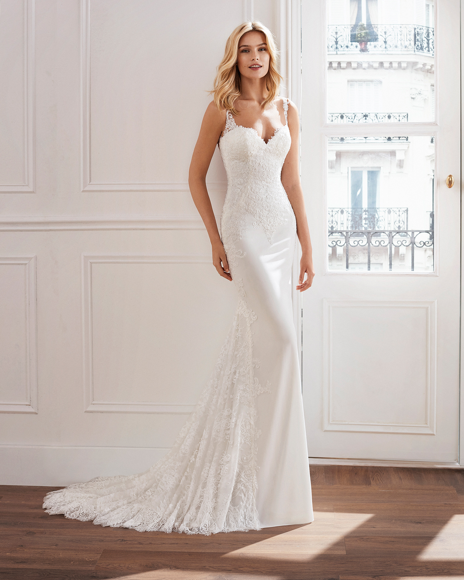 Sheath-style wedding dress in crepe. Beaded lace bodice and skirt with lace insets. Available in natural. 2019  Collection.