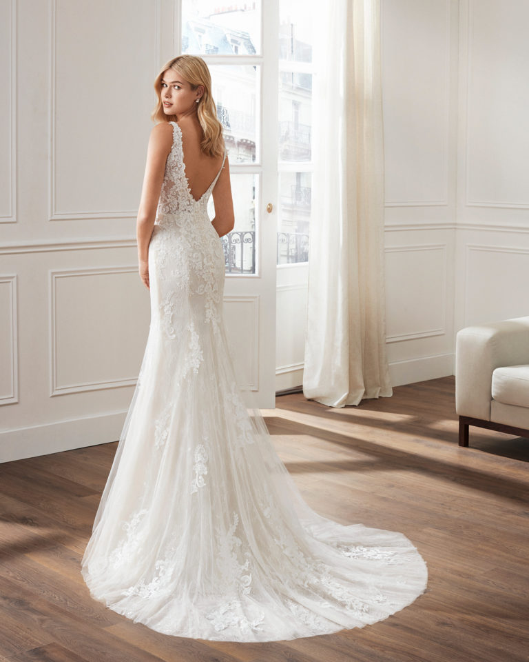 Mermaid-style wedding dress in beaded lace. V-neckline and appliquéd skirt. Available in natural. 2019  Collection.