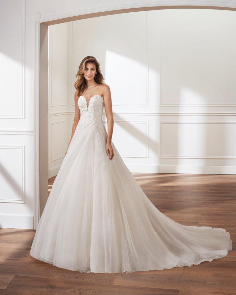 Vestido de novia corte linea A en garza. Escote en V profundo, cuerpo de encaje y falda de pliegues. Disponible en color natural. Colección  2019.